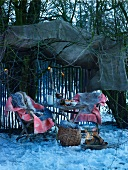 Snowy garden with fire bowl and blankets on garden chairs