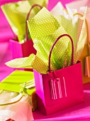 A green and pink gift bag with matching gift paper