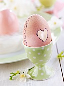 Easter egg decorated with heart in eggcup