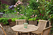Wooden table and chairs surrounded by plants on terrace