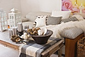 Decorative items on rustic coffee table in front of striped sofa with cushions and fur blanket