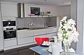 Esstisch mit weissen Lilien vor weisser Einbauküche im Designerstil