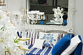 Baroque wall-mounted mirror below blue striped sofa with scatter cushions