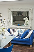 Ornate, Baroque-style wall-mounted mirror above blue sofa in eclectic kitchen-dining room with dark wood flooring