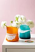 Vasen mit Tortenspitze verziert und Ranunkeln