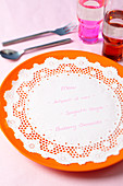 A doily used as a menu on a plate