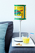 An original decorative lamp with a shade made from a colourful tin can