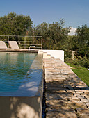 Pool with overflow and stone-flagged path in Mediterranean garden