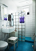 White bathroom with floor of blue mosaic tiles and glass brick shower partition