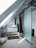 Modern bathroom with washstand and light, sliding partition construction in converted attic