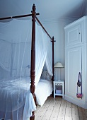 Antique four-poster bed with airy fabric canopy in rustic bedroom