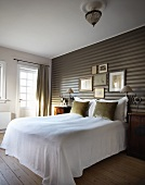 Elegant bedroom - bed with white throw against striped wallpaper