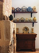 Old, stone fireplace and hand-made vases on shelves above antique cabinet