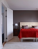 Bed with upholstered headboard and red bedspread against grey wall in modern bedroom with open door
