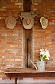 Hats hanging on pegs above watering can on rustic table against brick wall