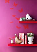 Red-painted shelves on purple-painted wall with butterfly motif
