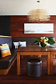 Corner bench upholstered in black leather and wooden table in dining room with wood-panelled walls and wooden floor