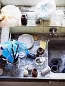 Top view of various jars and paintbrushes in dirty sink