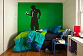 Teenager's bedroom with bed in front of painted figure on green wall