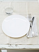 Place setting with white plate, cutlery and water glass