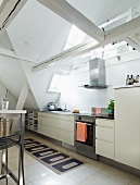 Modern kitchen below old roof beams