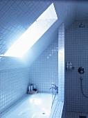 Unter Dachschräge eingebautes Bad mit weissen Fliesen an Wand, Badewanne und Boden