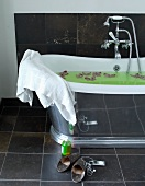 Vintage bathtub with reflective outer surface and slippers on grey tiled floor