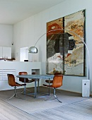 Shell chairs with leather covers and modern table in open-plan interior
