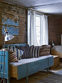Cushions on rustic sofa against wooden wall with peeling paint
