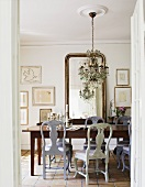 View into dining room with Rococo-style chairs through open door