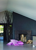Pink cushions on floor in front of open fireplace and black-painted wall