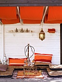 Chill-out area in Oriental-style living room with floor cushions below orange awnings on ceiling