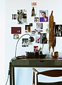 Moderner Schreibtisch aus dunklem Holz vor Wand mit angehefteten Photos