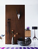 Animal trophy mounted on wooden partition and view of standard lamp in room beyond