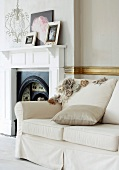 White upholstered sofa next to an open fireplace in a traditional room