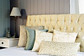 Upholstered headboard and pillows on front of a wooden wall
