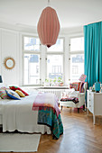 Bright bedroom with double bed below pendant lamp and comfortable armchair in bay window