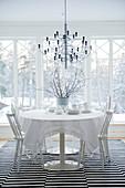 Designer Hängeleuchte über Esstisch und Stühle in Weiss auf Teppich mit schwarz-weissen Streifen