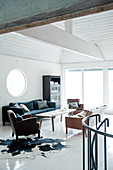 White loft interior flooded with light with wood-panelled tent roof above vintage seating on cow-skin rug