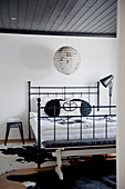 Antique-style metal bed and cow-skin rug below black-painted wooden ceiling and Japanese paper lampshade