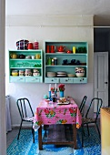 Colourful oilcloth on kitchen table below pastel green shelves on wall