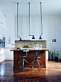 Vintage pendant lamps above wooden counter and bar stools in open-plan kitchen