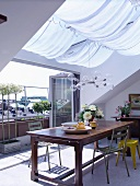 Dining area below skylight with awning in front of open, folding terrace doors