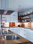 White kitchen with wooden work surfaces on island and base units