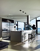 Designer kitchen with free-standing kitchen island in front of glass wall