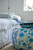 Beanbag with floral cover next to bed in rustic room