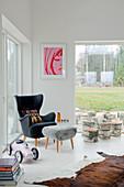 Grauer Ohrensessel im Fifiesstil mit Hocker und abgeschnittenen Baumstümpfen in modernem, weißem Wohnzimmer mit Gartenblick