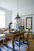 Solid wooden table and chair on blue and white patterned rug in rustic interior with vintage pendant lamp and stuffen penguin