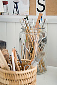 Glass jar and basket of various paintbrushes and writing utensils