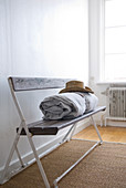 Rolled blanket and sun hat on vintage bench in corner of bedroom with sisal rug